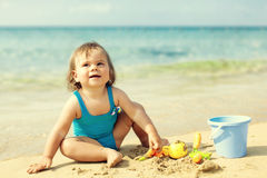 Little girl in blue swimsuit is playing in water Royalty Free Stock Images