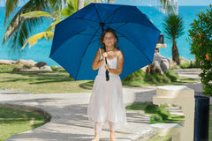 Little girl with blue umbrella enjoying her leisure time Royalty Free Stock Photo