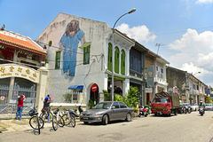 Little Girl in Blue on the wall. GEORGETOWN PENANG, MALAYSIA - JULY 30, 2015: Tourists are taking photos Little Girl in Blue Painted wall mural by artist Ernest Royalty Free Stock Image