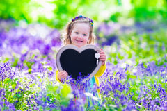 Little girl in bluebelss flowers Stock Images