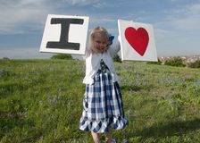 I Love You. Little girl in a bluebonnet flower field in Texas royalty free stock photo