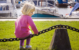 Little girl in boat marina stock photo