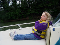 Little Girl Boat Ride. A cute little girl is enjoying a relaxing boat ride while deep in thought Royalty Free Stock Photography