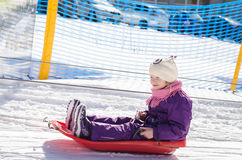 Little girl in bob-sleigh enjoying winter time. Lovely little child in purple overall sitting in bob-sleigh in ski tow Royalty Free Stock Photography