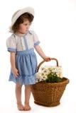 Little girl with bonnet. A little beautiful girl with bonnet, with a basket with flowers and toys Stock Photos