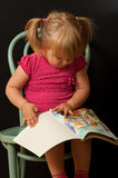 Little girl with book. Cute little girl sitting on green chair with a colourful book Royalty Free Stock Images