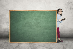 Little girl with book and blank chalkboard Royalty Free Stock Photo