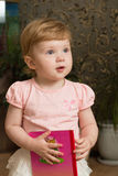 Little girl with a book. On dark background Royalty Free Stock Photos