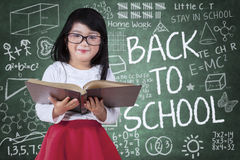 Little girl with book and doodles on chalkboard Royalty Free Stock Image