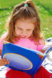 Little girl with a book in the garden Stock Photography