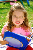 Little girl with a book in the garden Royalty Free Stock Photography