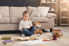 Little girl with book and her favorite toy at home Royalty Free Stock Photography