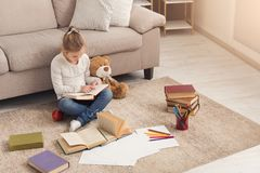 Little girl with book and her favorite toy at home Stock Photo