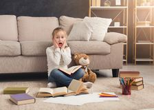Little girl with book and her favorite toy at home Royalty Free Stock Images