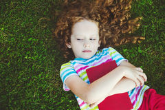 Little girl with a book lying in the grass in summer park Royalty Free Stock Image