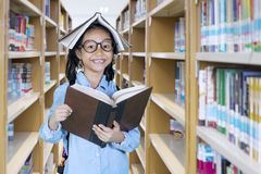 Little girl with a book over her head. Picture of little girl looking at the camera with a book over her head while standing in the library Royalty Free Stock Photos