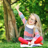 Little girl with a book in a park wearing glasses pointing at co Royalty Free Stock Images
