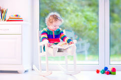 Little girl with a book in a rocking chair. Cute curly little girl, funny toddler wearing a warm colorful knitted dress reading a book relaxing in a white Stock Image