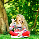 Little girl with book in the summer park Royalty Free Stock Photography