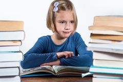 Little girl with a book on a white background. Little girl at a desk with a book learning on a white background Stock Photo
