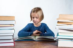 Little girl with a book on a white background. Little girl at a desk with a book learning on a white background Royalty Free Stock Images