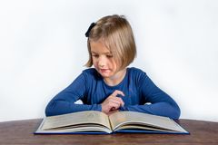 Little girl with a book on a white background. Little girl at a desk with a book learning on a white background Stock Photography