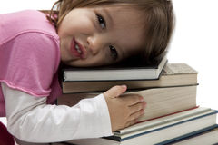 Little girl with books. Little girl huga  tower of colorfull isolated books Stock Photography