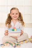 Little girl with books and alphabet wooden blocks Royalty Free Stock Image