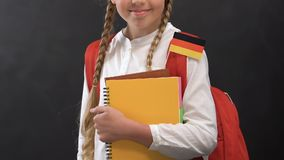 Little girl with books and German flag smiling at camera, language studying. Stock footage stock video footage