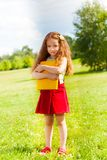 LIttle girl with books in park Stock Photo