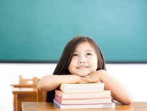 little girl with books and thinking in classroom stock images