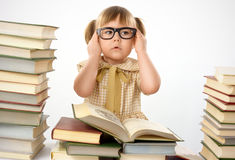 Little girl with books wearing black glasses Stock Photos