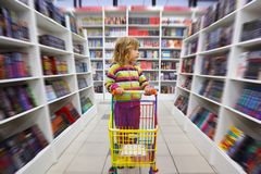 Little girl in bookshop, with cart for goods. There is one among racks Stock Photography