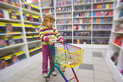 Little girl in bookshop, with cart for purchases Stock Photo