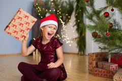 Little girl sitting near Christmas tree with gift in her hands royalty free stock images