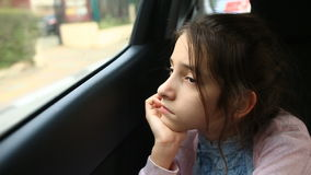 Little girl bored in car - staring into space through window - great reflections of passing trees.  stock video footage