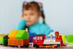 Little girl bored playing with toys alone Stock Image