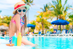 Little girl with bottle of sun cream sitting on the edge of swimming pool. Little adorable girl in swimsuit with suntan lotion bottle Royalty Free Stock Photography