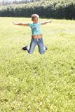 Little girl. Bounce. Juicy green grass. Happy smile. Summer. Sunny Stock Photo