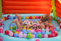 Little girl in a bouncy castle Stock Images
