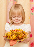 Little girl with bouquet. The little girl looks at the bouquet of autumn leaves Royalty Free Stock Photography