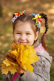 Little girl with bouquet of autumn leaves Stock Photo