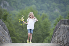 Little girl with a bouquet of daisies walking outdoors Royalty Free Stock Images