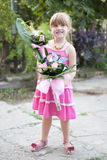 Little girl with a bouquet of flowers. Happy smiling little girl with a bouquet of flowers Stock Photos
