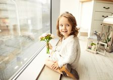 A little girl with a bouquet of flowers on her mother`s day sit Royalty Free Stock Image