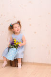 Little girl with bouquet of flowers indoors Stock Images