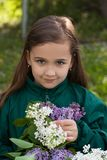 Little Girl With Bouquet Of Lilac Flowers In Garden. Royalty Free Stock Images