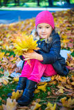 Little girl with bouquet of maple leaves in autumn park Royalty Free Stock Photo