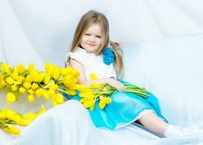 Little girl with bouquet of tulips stock photo