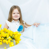 Little girl with bouquet of tulips Stock Image